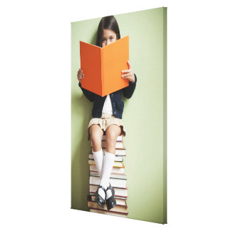 Mixed race girl sitting on stack of books canvas print