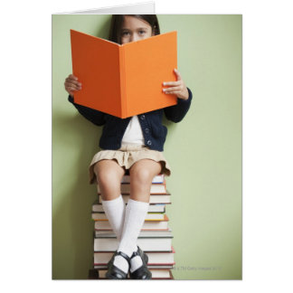 Mixed race girl sitting on stack of books greeting cards