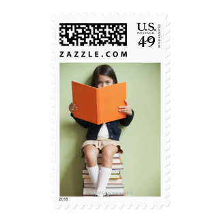 Mixed race girl sitting on stack of books postage stamps
