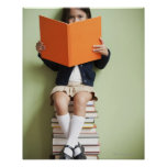 Mixed race girl sitting on stack of books print