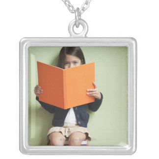 Mixed race girl sitting on stack of books silver plated necklace