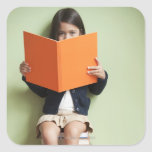 Mixed race girl sitting on stack of books square sticker