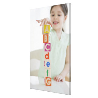 Mixed race girl stacking alphabet blocks stretched canvas print