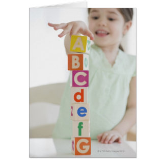 Mixed race girl stacking alphabet blocks greeting card