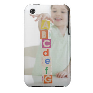 Mixed race girl stacking alphabet blocks iPhone 3 covers
