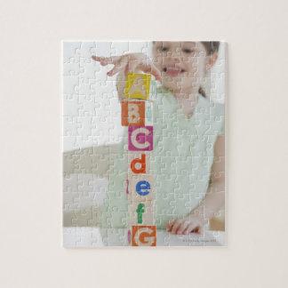 Mixed race girl stacking alphabet blocks jigsaw puzzle