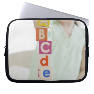 Mixed race girl stacking alphabet blocks laptop computer sleeves