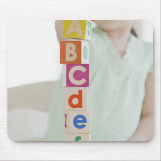 Mixed race girl stacking alphabet blocks mouse pad