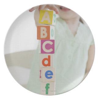 Mixed race girl stacking alphabet blocks plate