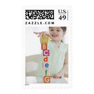 Mixed race girl stacking alphabet blocks stamp