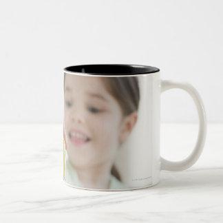 Mixed race girl stacking alphabet blocks Two-Tone coffee mug