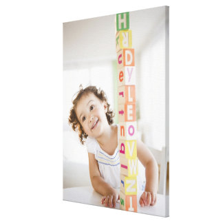 Mixed race girl stacking blocks canvas print