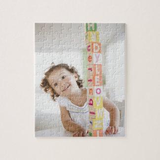 Mixed race girl stacking blocks jigsaw puzzle