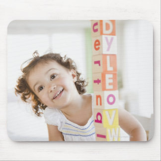 Mixed race girl stacking blocks mouse pad
