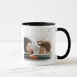 Mixed race mother reading book to son mug