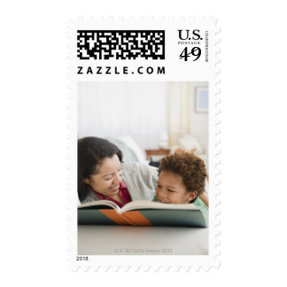 Mixed race mother reading book to son stamps