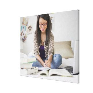 Mixed race teenage girl doing homework on bed canvas print
