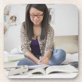 Mixed race teenage girl doing homework on bed coaster