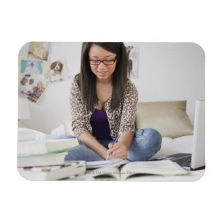 Mixed race teenage girl doing homework on bed magnet