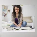 Mixed race teenage girl doing homework on bed print