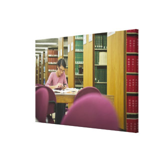Mixed race woman doing research in library 2 canvas print