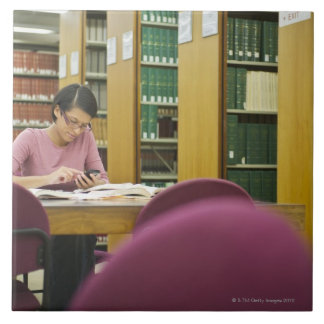 Mixed race woman doing research in library 2 ceramic tile