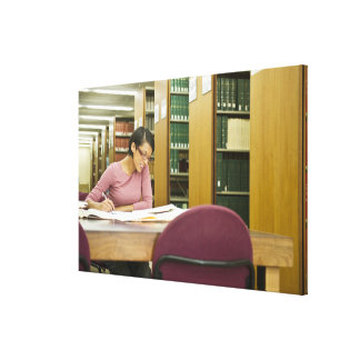 Mixed race woman doing research in library canvas print