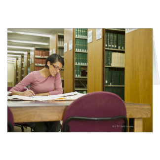 Mixed race woman doing research in library greeting cards