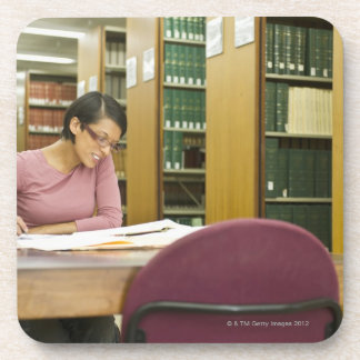 Mixed race woman doing research in library coaster