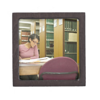 Mixed race woman doing research in library jewelry box