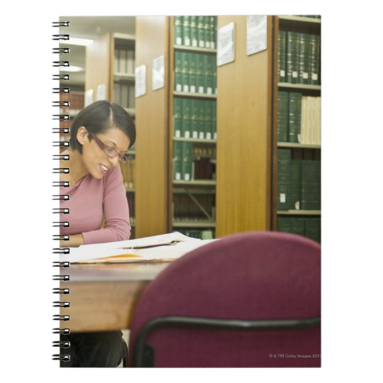 Mixed race woman doing research in library notebook