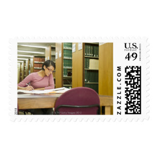 Mixed race woman doing research in library stamps