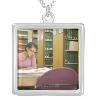 Mixed race woman doing research in library square pendant necklace