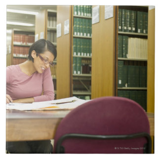 Mixed race woman doing research in library ceramic tile
