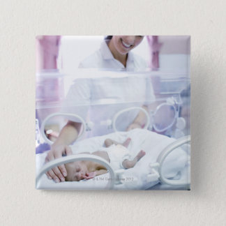 MODEL RELEASED. Nurse and premature baby. Button