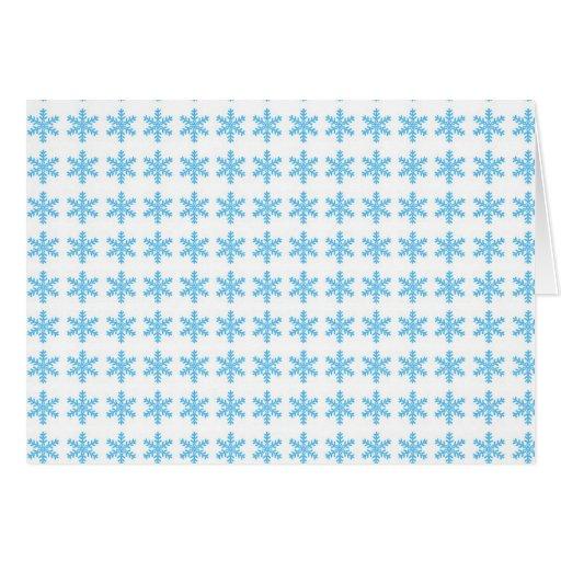 Modelo azul del copo de nieve con el fondo blanco tarjeta de felicitación