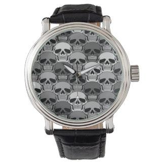 Modelo gris del cráneo que entrelaza relojes de mano