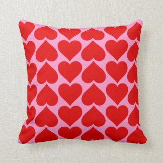 Modelo rojo del corazón en color rosado del cojín decorativo