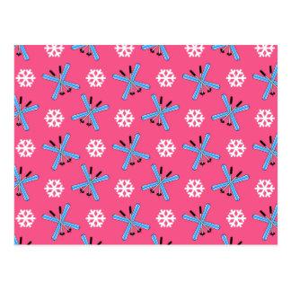 Modelo rosado de los esquís y de los copos de niev postal
