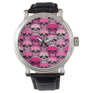 Modelo rosado del cráneo que entrelaza relojes de pulsera
