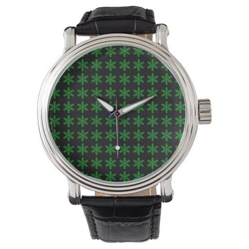 Modelo verde del copo de nieve con el fondo negro relojes de mano