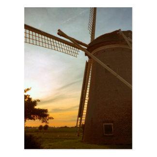 Molino de viento en la puesta del sol tarjeta postal