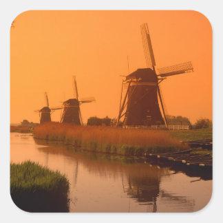 Molinoes de viento en la puesta del sol, pegatina cuadrada