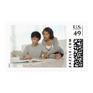 mom helping son with homework postage stamps