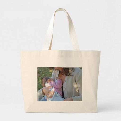 Momia triguena joven bonita que amamanta a su bebé bolsa tela grande
