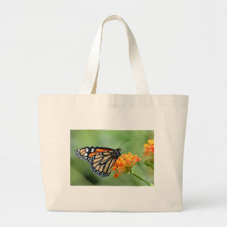 Monarch butterfly feeding on flower large tote bag