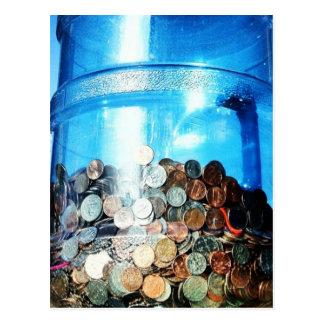 Monedas del dinero ahorradas en una postal del jar
