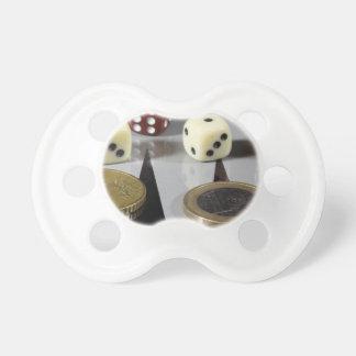 Monedas en un tablero de backgammon chupete