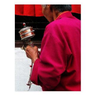 Monja budista tibetana con la rueda de rezo postales