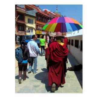 Monje tibetano con el paraguas colorido postal